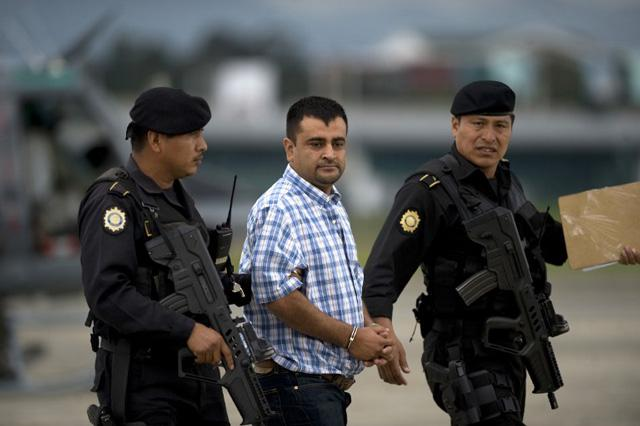 GUATEMALA, Guatemala City : Police take into custody alleged drug trafficker Walter Arelio Montejo Merida (C), aka Zope, related to the Mexican Sinaloa drug cartel, who faces an extradition warrant from the United States, upon their arrival at the air force base in Guatemala City on June 10 , 2012. AFP PHOTO Johan ORDONEZ